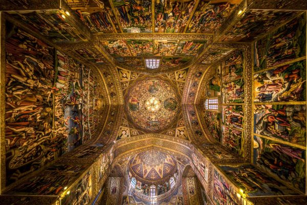 Vank Cathedral, a cathedral in Isafan city, Jolfa district, was built during Safavid dynasty by Armenians who were resettled in Isfahan following Shah Abbas II's order. This cathedral is ornamented by various forms of art from which the most significant ones are the delicate blue and gilded paintings on the ceiling and central dome depicting the Biblical story of creation of the world. The paintings on the wall are inspired by Italian paintings. The church is still used by Armenians of Isfahan in current day and is open for visits as well. I was amazed by the golden color of the ceiling and also unique paintings all around. I putted my camera on the floor and it was oriented to up. For capturing this photo, I used wide lens.